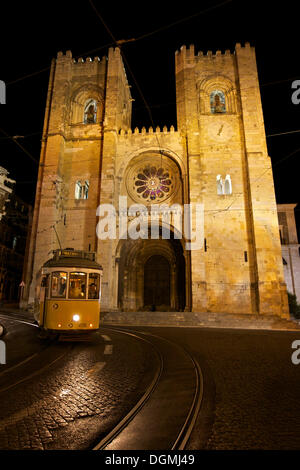 Yellow tram line No. 28 in front of the Sé Cathedral, Catedral Sé Patriarcal, at night, Lisbon, Portugal, Europe - Stock Photo