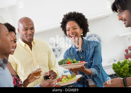 An informal office event. People handing plates of food across a buffet table. - Stock Photo