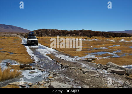 Off-road vehicle driving through an icy ford, Altiplano, Potosi, southern Bolivia, South America - Stock Photo