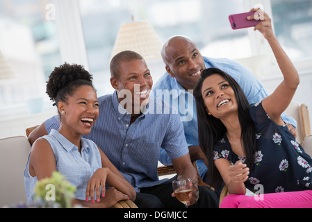 Office Event. A woman taking a selfie of the group with a pink smart phone. - Stock Photo