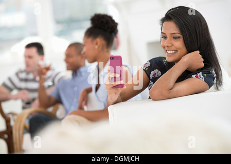 Office event. A woman using her pink smart phone. - Stock Photo