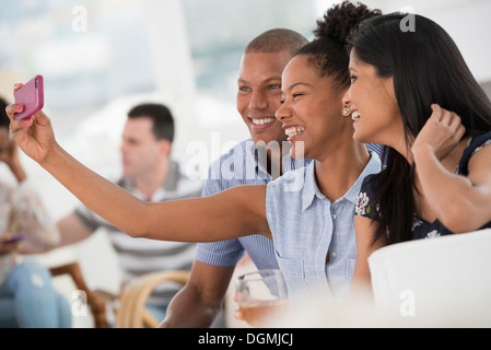 Office event. A woman taking a selfie of the group with a smart phone. - Stock Photo