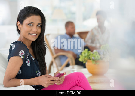 Office event. A woman seated on the sofa using her smart phone.