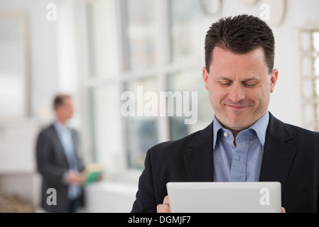 Business people. A man in a dark suit using a digital table. - Stock Photo