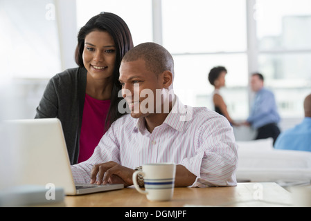 Office. Two people, a man and a woman, sharing a laptop computer. - Stock Photo