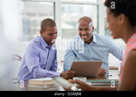Office life. Three people working around a table, using digital tablets and laptops. - Stock Photo