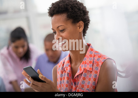 Office life. A woman using a smart phone. - Stock Photo