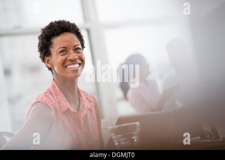 Office life. A young woman in a pink shirt laughing. - Stock Photo