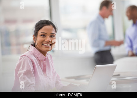 Office life. A woman sitting at a desk using a laptop computer. Two men in the background. - Stock Photo