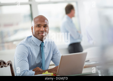 Office life. Businessman in a shirt and tie sitting at a desk, using a laptop computer. - Stock Photo