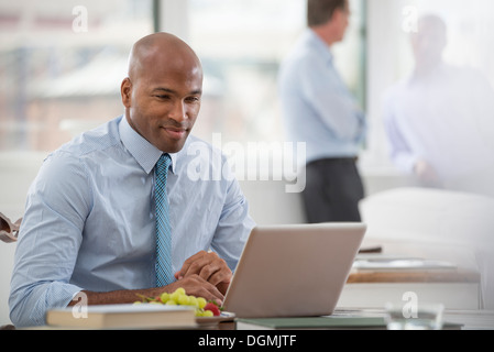 Office life. A businessman in a shirt and tie sitting at a desk, using a laptop computer. - Stock Photo