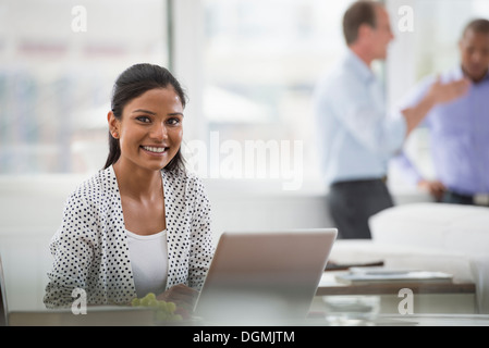 Office life. A woman sitting at a desk using a laptop computer. Two men in the background.