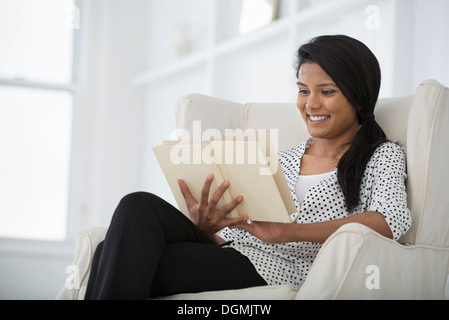 Office life. A woman sitting on a sofa, using a digital tablet. - Stock Photo