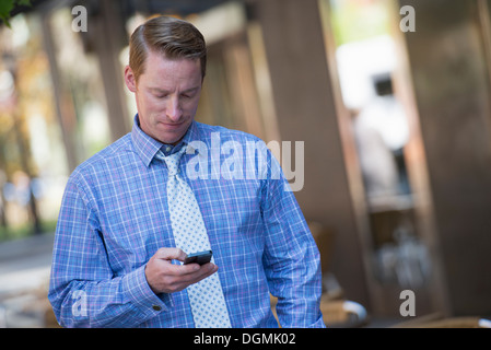 A businesswoman and two businessmen outdoors in the city. - Stock Photo
