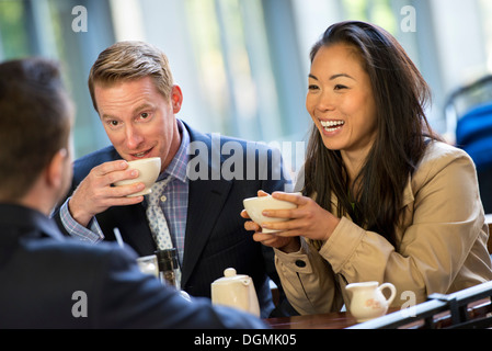 A businesswoman and two businessmen sitting in a coffee shop having a cup of coffee. - Stock Photo