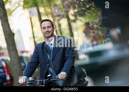 A man in a business suit, outdoors in a park. Sitting on a bicycle. - Stock Photo