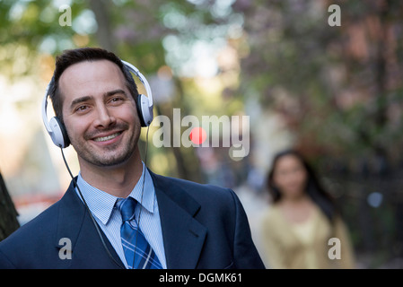 A man in a business suit wearing white headphones, listening to music. - Stock Photo