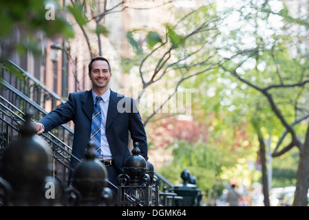A man in a business suit standing on the steps on a street. - Stock Photo