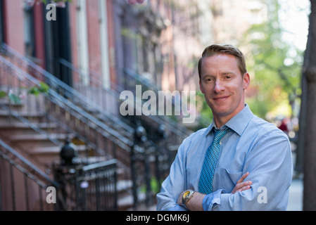 A man in a blue shirt and blue tie with arms folded, standing on the sidewalk - Stock Photo