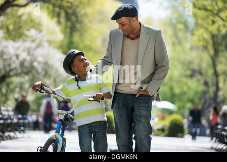 Bicycling and having fun. A father and son side by side. - Stock Photo