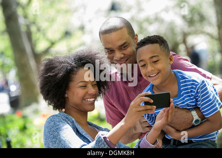 A family in the park on a sunny day. Taking photographs with a smart phone. - Stock Photo
