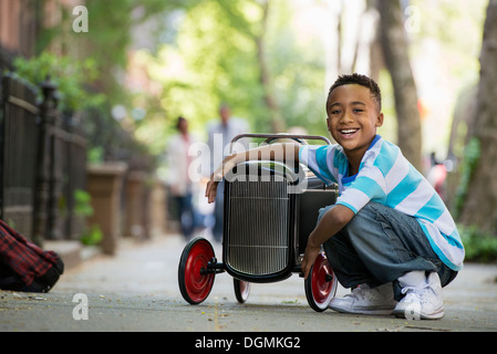 A young boy playing with a old fashioned toy car on wheels on a city street. - Stock Photo