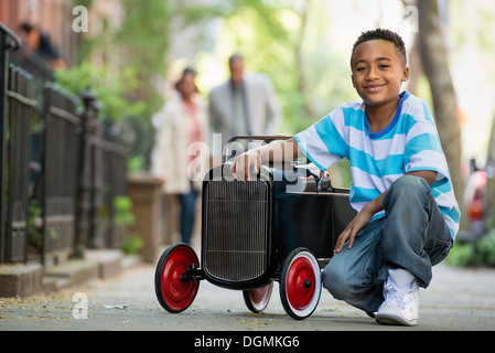 A young boy playing with a old fashioned toy car on wheels on a city street. A couple looking on. - Stock Photo