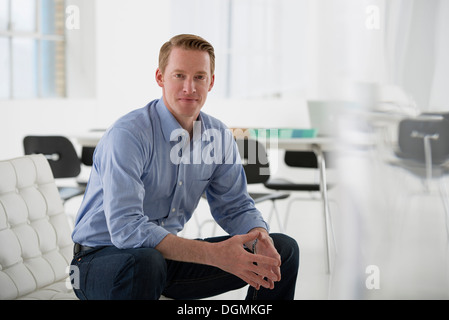 Business. A man in a blue shirt sitting down. - Stock Photo