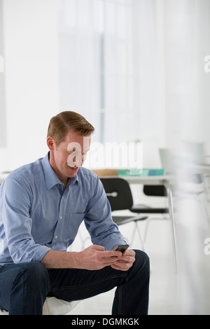 A man seated, checking his smart phone for messages and texting. - Stock Photo