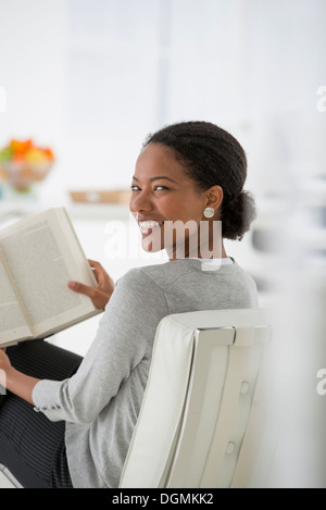 Business. A woman sitting and reading a book. Research or relaxation. Looking over her shoulder and smiling. - Stock Photo