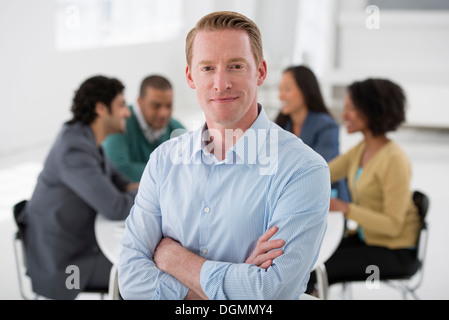 Business meeting. A group sitting down around a table. A man smiling confidently. - Stock Photo