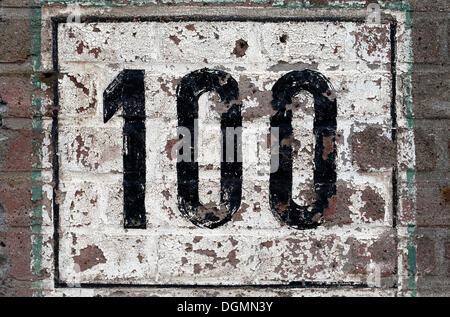 Street number 100 painted on a brick wall, weathered - Stock Photo