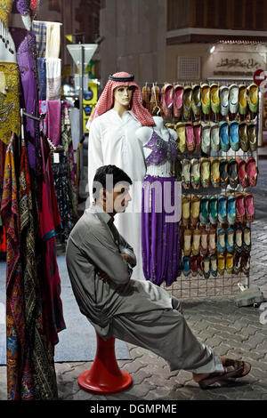 Salesman sitting bored in front of his shop, Deira Old Souk, United Arab Emirates, Middle East, Asia - Stock Photo