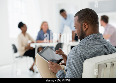 Office interior. Meeting. One person seated separately, using a tablet computer. Holding a digital tablet. - Stock Photo