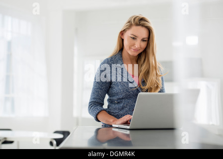 Office interior. A woman sitting at a table using a digital tablet. - Stock Photo