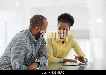 Office interior. Two people, a couple at a table using a digital tablet. - Stock Photo