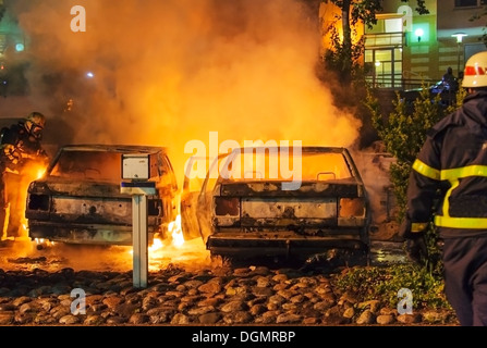 Burning cars and fire fighters - Stock Photo