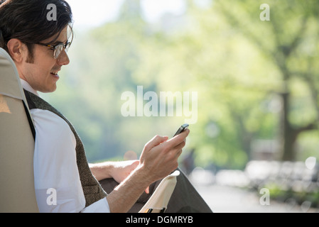 City life. A man sitting in a canvas camping chair in the park looking at his cell phone. - Stock Photo