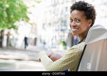 City life. A woman sitting in a camping chair in a city park looking over her shoulder. - Stock Photo