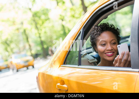 A woman sitting in the rear passenger seat of a yellow cab, checking her smart phone. - Stock Photo