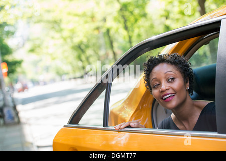 A woman getting out of the rear passenger seat of a yellow cab. - Stock Photo