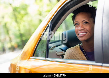 A woman sitting in the rear passenger seat of a yellow cab. - Stock Photo