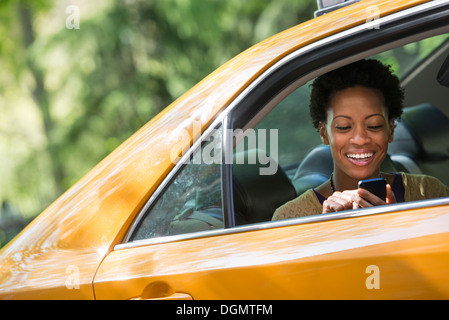 A woman sitting in the rear passenger seat of a yellow cab, checking her phone. - Stock Photo