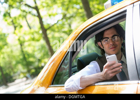 A young man in the back seat of a yellow cab, looking at his smart phone. - Stock Photo