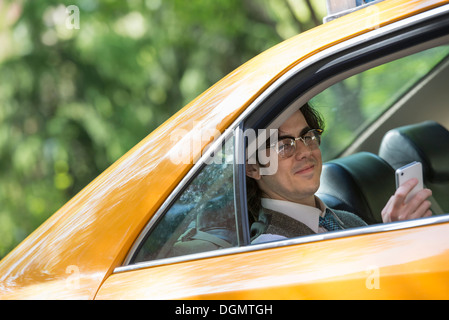 City life. People on the move. A young man in the back seat of a taxi. - Stock Photo