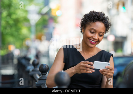 People on the move. A woman in a black dress on a city street, checking her phone. - Stock Photo
