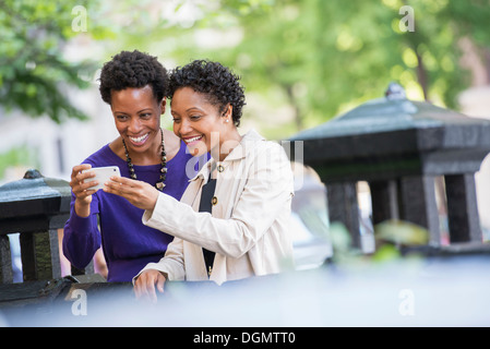 City life. Two women sitting on a park bench, looking at a smart phone. - Stock Photo