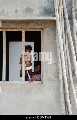 Young Indian baby girl standing in a window frame in a rural indian village. Andhra Pradesh, India - Stock Photo