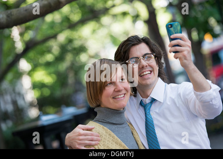 City. Two people, a man and woman outdoors, side by side posing for a photograph using his smart phone. - Stock Photo