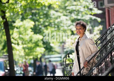 City. A woman walking down steps outside a town house. - Stock Photo